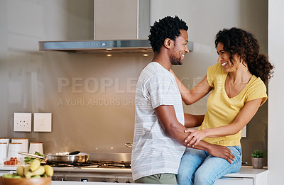 Buy stock photo Cropped shot of a young married couple being affectionate in the kitchen at home