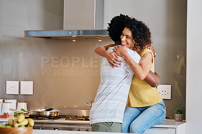 Buy stock photo Cropped shot of a young married couple embracing each other in the kitchen at home