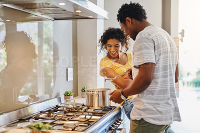 Buy stock photo Cropped shot of a young married couple cooking together in the kitchen at home