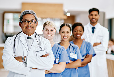 Buy stock photo Portrait of a group of medical practitioners standing in a row in a hospital