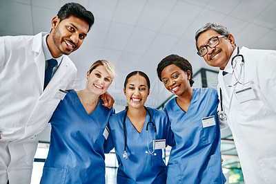 Buy stock photo Portrait of a group of medical practitioners huddled together in a hospital