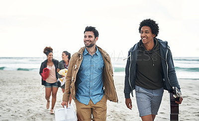 Buy stock photo Shot of a group of young friends walking together along the beach