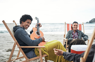 Buy stock photo Shot of a young man playing the guitar while hanging out with friends at the beach
