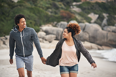 Buy stock photo Shot of a happy young couple running on the beach