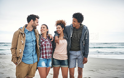 Buy stock photo Shot of a group of young people spending a day at the beach