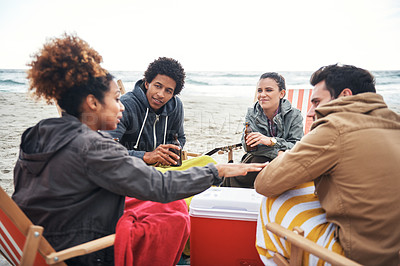 Buy stock photo Shot of a group of young friends hanging out at the beach