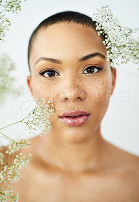 Buy stock photo Studio portrait of a beautiful young woman posing amongst delicate flowers