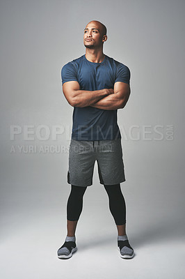 Buy stock photo Studio shot of an athletic young man standing with his arms crossed against a grey background