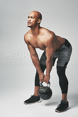 Buy stock photo Studio shot of an athletic young man working out with a kettle bell against a grey background