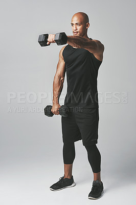 Buy stock photo Studio shot of an athletic young man working out with dumbbells against a grey background