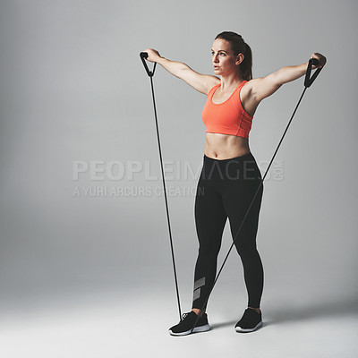 Buy stock photo Studio shot of an athletic young woman working out with a resistance band against a grey background