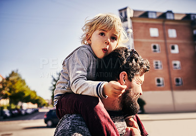Buy stock photo Cropped shot of a young man piggybacking his adorable little son through the city