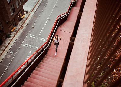 Buy stock photo High angle shot of an athletic young woman running up a flight of stairs while exercising in the city