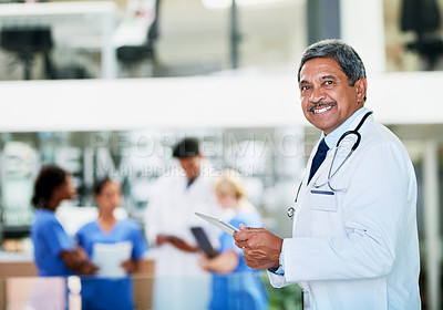 Buy stock photo Portrait of a healthcare worker standing in a hospital with colleagues in the background