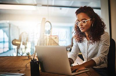 Buy stock photo Shot of a young businesswoman using a laptop during a late night at work