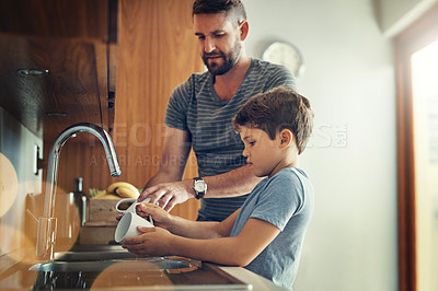 Buy stock photo Shot of a father and son washing dishes together at home