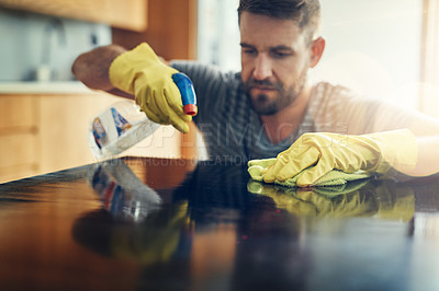Buy stock photo Shot of a handsome young man cleaning his home