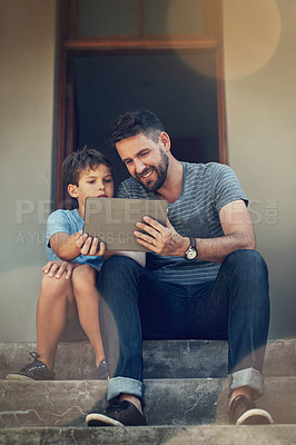 Buy stock photo Shot of a father and son using a digital tablet together on the front steps of their home