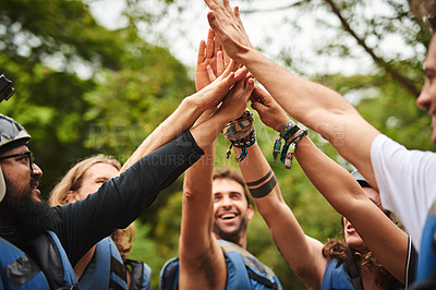 Buy stock photo Cropped shot of a group of young friends high fiving while out white water rafting