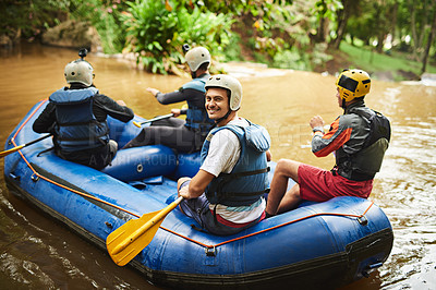 Buy stock photo High angle portrait of a handsome young man and his friends sitting in their white water raft