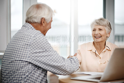 Buy stock photo Cropped shot of an affectionate senior couple shaking hands while working on their finances at home