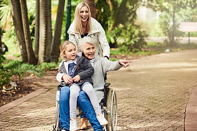 Buy stock photo Shot of a senior woman spending time with her family while being pushed around in her wheelchair