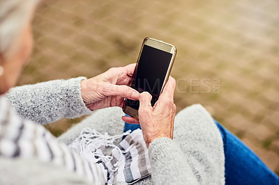 Buy stock photo Shot of an unrecognizable woman using her cellphone outdoors