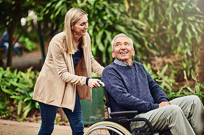 Buy stock photo Shot of a woman pushing her father around in his wheelchair