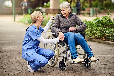 Buy stock photo Shot of a female nurse spending time with a senior woman in a wheelchair in the garden
