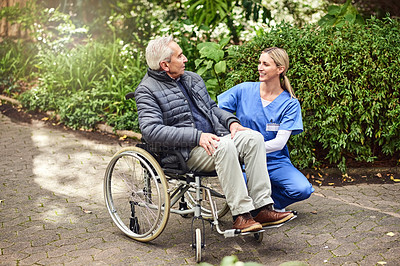 Buy stock photo Shot of a female nurse spending time with a senior man in a wheelchair in the garden