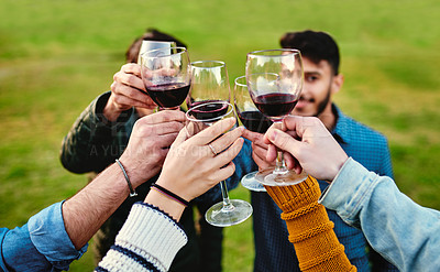 Buy stock photo Cropped shot of a group of friends toasting with wine glasses outdoors