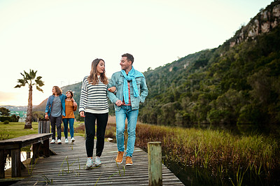 Buy stock photo Shot of young couples walking on a pier outdoors