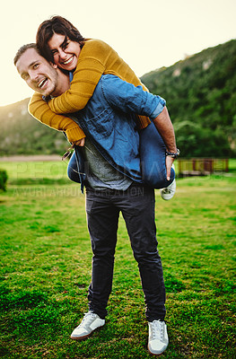 Buy stock photo Shot of a young man giving his girlfriend a piggyback ride outdoors