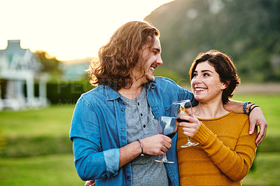 Buy stock photo Cropped shot of a young couple making a toast outdoors