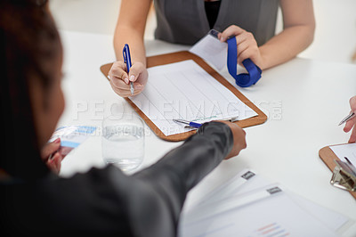 Buy stock photo Over the shoulder shot of a businesswoman holding a form for a client to sign to attend a seminar inside of a building during the day