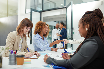 Buy stock photo Shot of a confident young businesswoman holding a form for a client to sign to attend a seminar inside of a building during the day
