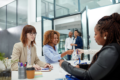 Buy stock photo Shot of a group of focused young businesswomen signing forms to attend a seminar inside of a building during the day