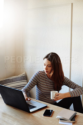 Buy stock photo Shot of an attractive young woman using a laptop while working at home