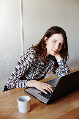 Buy stock photo Portrait of an attractive young woman using a laptop while working at home