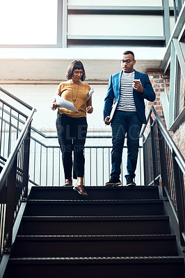 Buy stock photo Shot of two designers having a discussion on a staircase in an office