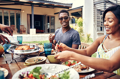 Buy stock photo Shot of a happy family having lunch out in the backyard