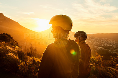 Buy stock photo Rearview shot of two female friends out skating at sunset