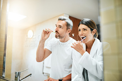 Buy stock photo Cropped shot of a mature couple brushing their teeth together in their bathroom