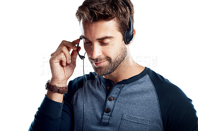 Buy stock photo Studio shot of a handsome young man using a headset against a white background