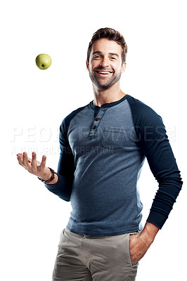 Buy stock photo Studio portrait of a handsome young man tossing an apple against a white background