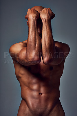 Buy stock photo Studio shot of an unrecognizable muscular young man posing nude with his arms covering his face against a grey background