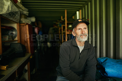 Buy stock photo Shot of a mature man standing in the shed on a farm