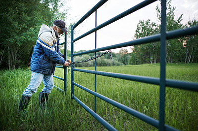 Buy stock photo Shot of a mature man locking the gate with chains on a farm