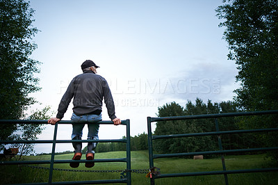 Buy stock photo Rearview shot of a mature man sitting on top of a fence on the farm