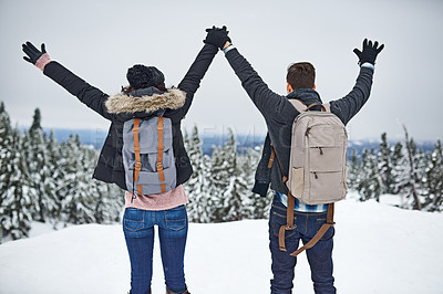 Buy stock photo Shot of a happy young couple enjoying themselves while being out in the snow